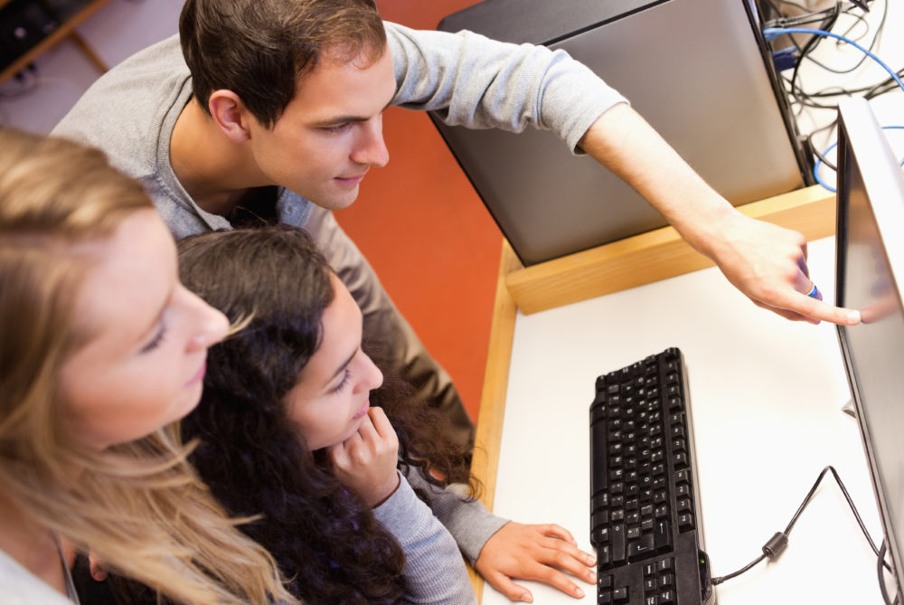 Fellow students using a computer in an IT room